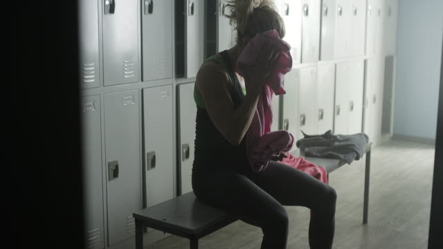athlete female wiping sweat from forehead in locker room - forehead stock videos and b-roll footage