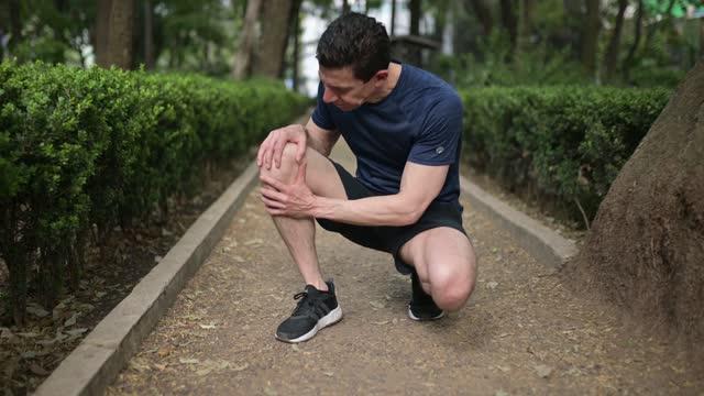 athlete having pain in the knee - injured stock videos & royalty-free footage
