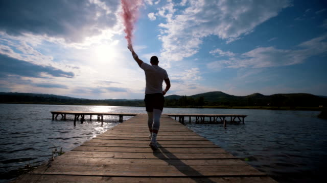 athlete holding flaming torch on lake dock - flaming torch stock videos & royalty-free footage