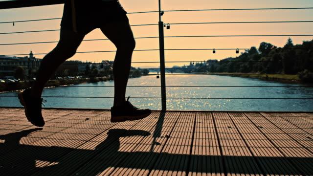 SLO MO atleta jogging ao longo da ponte pelo anoitecer