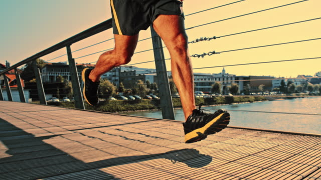 SLO MO Athlete jogging across the bridge in city