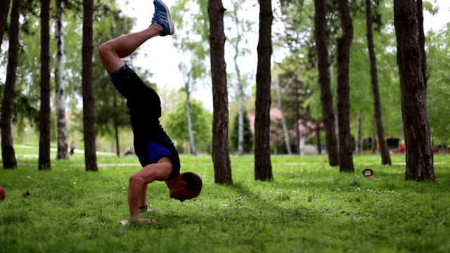 Athlete man exercising and doing hand stand outdoors in a park