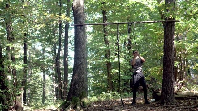 stockvideo's en b-roll-footage met atleet op gymnastiek ringen in een forest - oefeningen met lichaamsgewicht