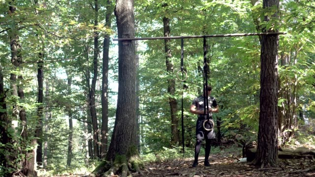 athlete on gymnastic rings in a forest - gymnastic rings stock videos & royalty-free footage
