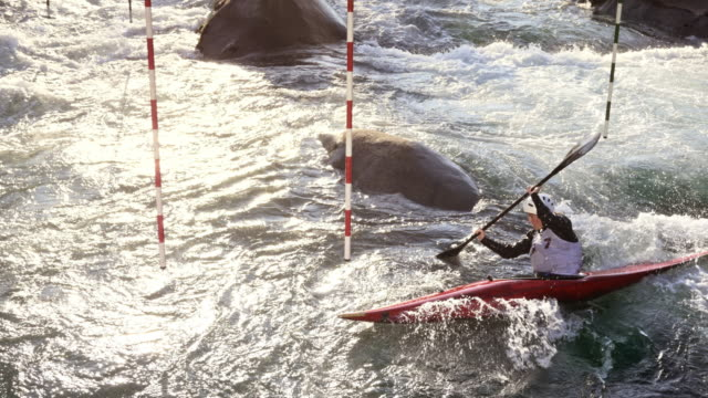vídeos de stock, filmes e b-roll de aerial athlete paddling through the gates in a canoe slalom competition - canoagem