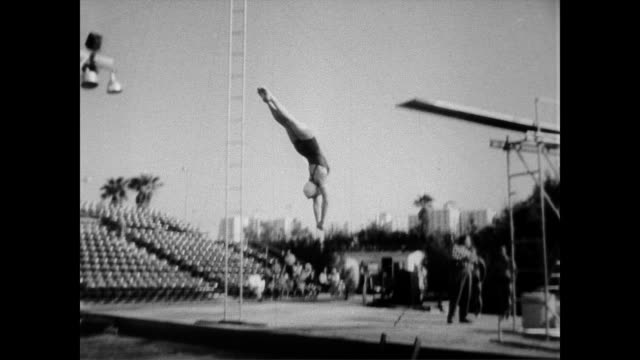 stockvideo's en b-roll-footage met / athlete pat mccormick dives from the high board in front of audience olympic diver pat mccormick makes professional debut on april 08 1957 in los... - 1957