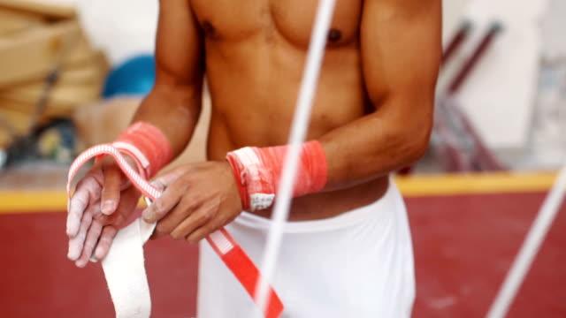 Athlete puting sporst tape around wrist and prepring  himself for training