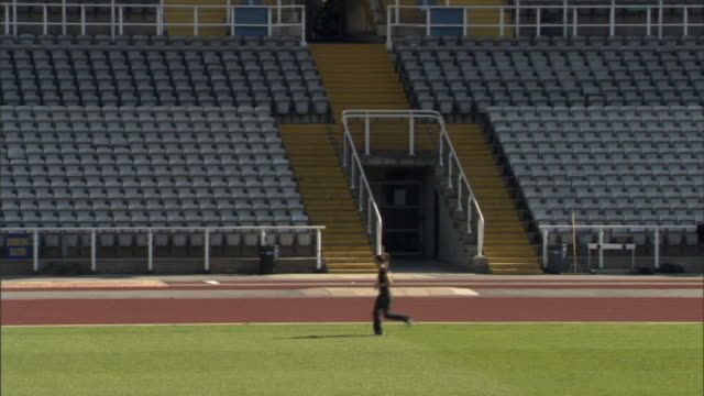 ws athlete running in empty stadium/ sheffield, england - zolla video stock e b–roll