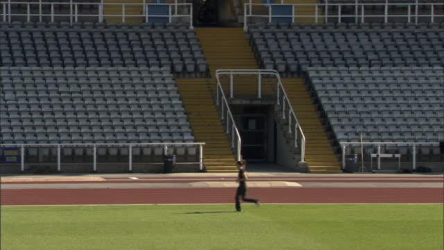 ws athlete running in empty stadium/ sheffield, england - turf stock videos & royalty-free footage