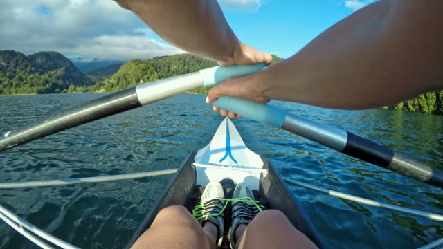 POV Athlete sculling on a sunny lake