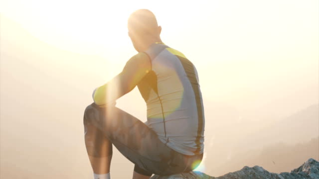athlete sits on top of the mountain and thinking - pursuit sports competition format stock videos & royalty-free footage
