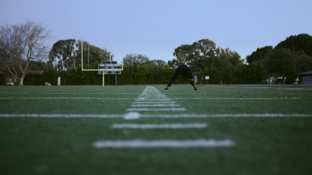 athlete stretching on a football field in the morning. - american football pitch stock videos & royalty-free footage