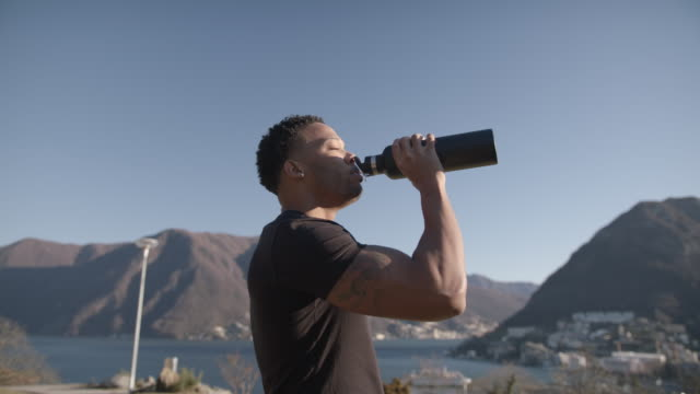 athlete takes a break from workout to drink from water bottle - flasche stock-videos und b-roll-filmmaterial