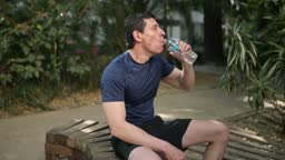 Athlete taking break and drinking water from the bottle