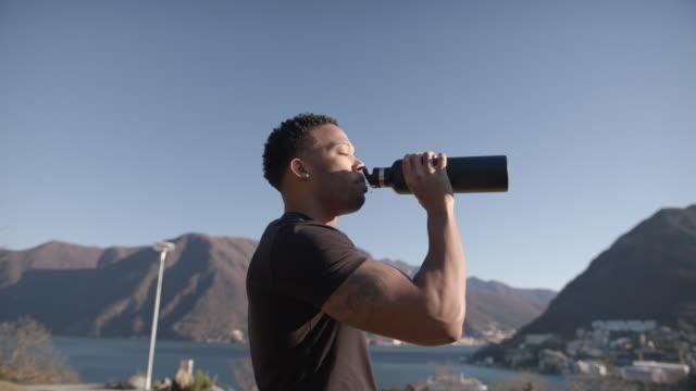 vidéos et rushes de entraînement d'athlète, prend la pause pour boire de la bouteille d'eau - bouteille d'eau minérale
