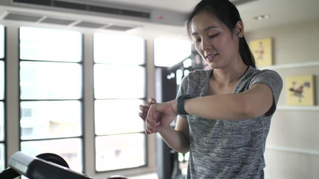 vídeos de stock e filmes b-roll de athlete using smart watch for analyzing her performance - ciclo