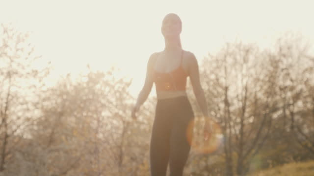 athlete walking with headphones at sunset - public park stock videos & royalty-free footage