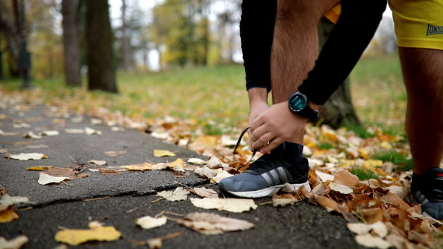 vídeos de stock, filmes e b-roll de atleta usando relógio inteligente enquanto amarrar seus sapatos - laço acessório
