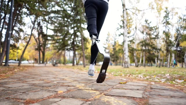 athlete with a artificial leg running in a city park - artificial limb stock videos & royalty-free footage