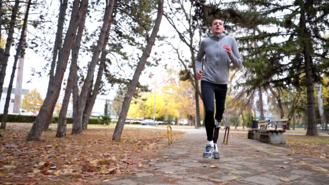 Athlete with a artificial leg running outdoors in a park