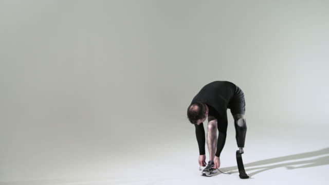 athlete with prosthetic leg tying shoelace - amputee stock videos & royalty-free footage