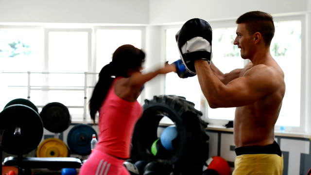 Athlete woman and fitness instructor on boxing training