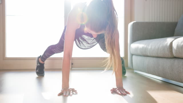 athlete woman doing plank jumping jack exercise on living room floor - plank stock videos & royalty-free footage