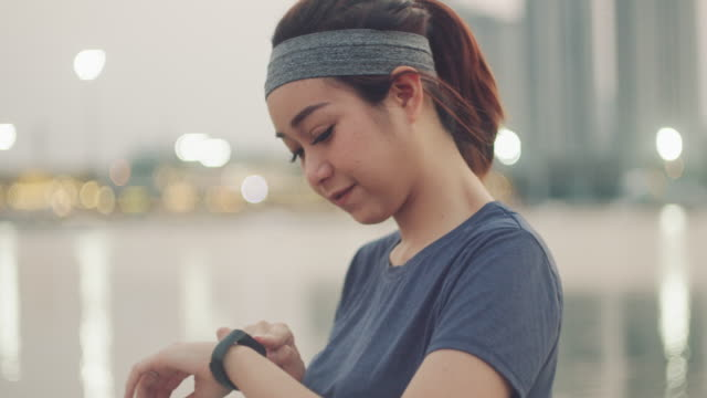 athlete woman using smart watch at river city. - watch timepiece stock videos & royalty-free footage