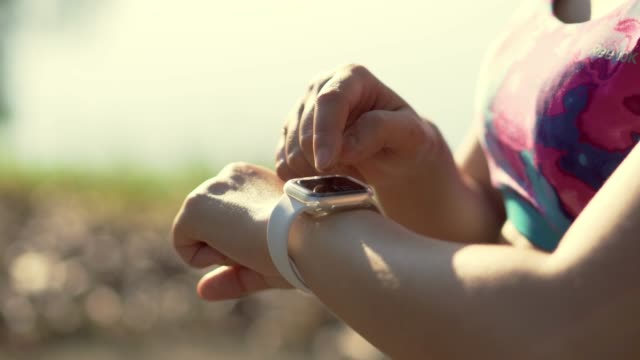 sportlerinnen, die nach dem joggen im morgen im park die smart-watch überprüfen - armband stock-videos und b-roll-filmmaterial