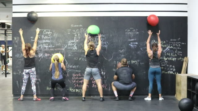 Athletes exercising with medicine balls at gym