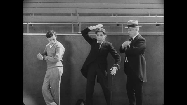 stockvideo's en b-roll-footage met 1927 athlete's (buster keaton) failure at the discus causes tension between unaware bystanders - verwijten