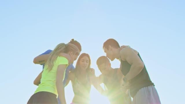 athleten, die beim sonnenuntergang gegen klaren himmel huddeln - nah stock-videos und b-roll-filmmaterial