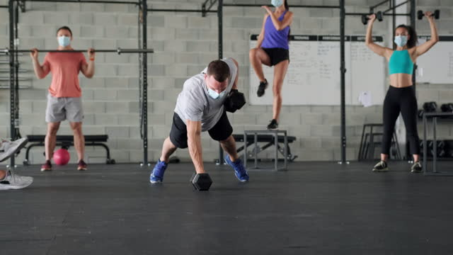 athletes in 20s and 30s working out at gym in surgical masks - bodyweight training stock videos & royalty-free footage