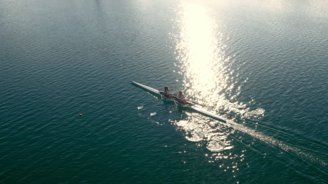 aerial athletes in double scull gliding across a lake in sunshine - rowing stock videos & royalty-free footage