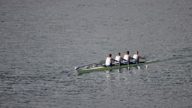 Athletes in quad scull gliding across a lake