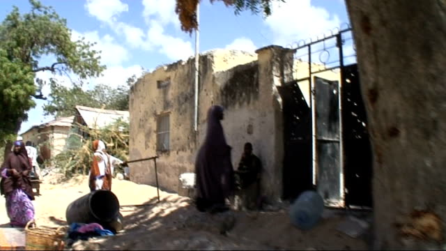 Athletes in training for London 2012 Olympic Games TRACK ALONG past rubble outside wrecked buildings as gunfire from Al Shabaab snipers heard SOT...