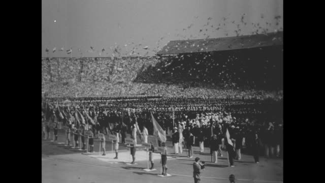 Athletes parade at opening ceremony of 1948 Summer Olympics at London's Wembley Stadium / WS stadium with packed stands and more spectators at center...