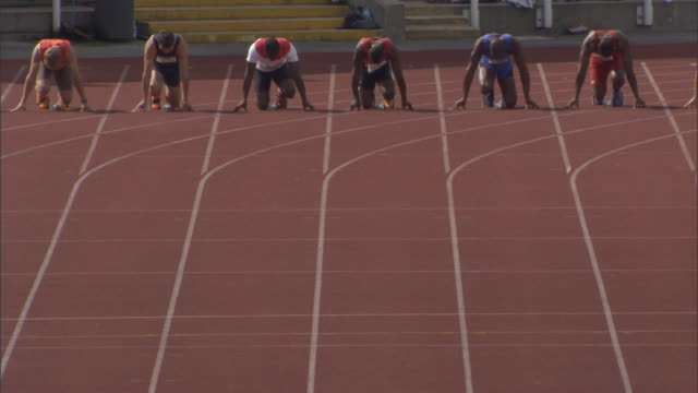ha ws pan cu athletes preparing at starting block and running in sprint, then winner celebrates / sheffield, england, uk - スポーツマン点の映像素材/bロール