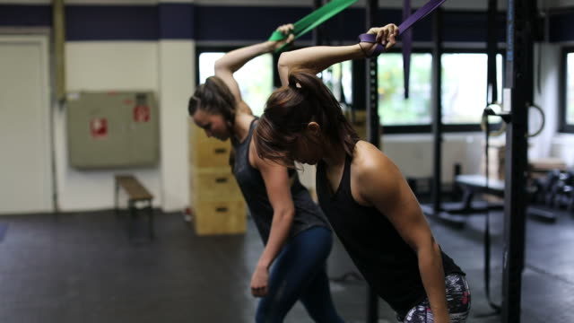 athletes pulling resistance bands in gym - pampering self stock videos and b-roll footage
