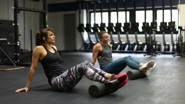athletes rolling legs on foam rollers in gym - pampering self stock videos and b-roll footage