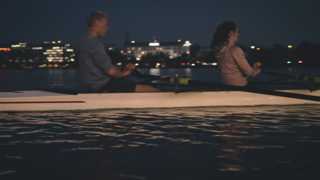 athletes rowing boat in river at night - sculling stock videos & royalty-free footage