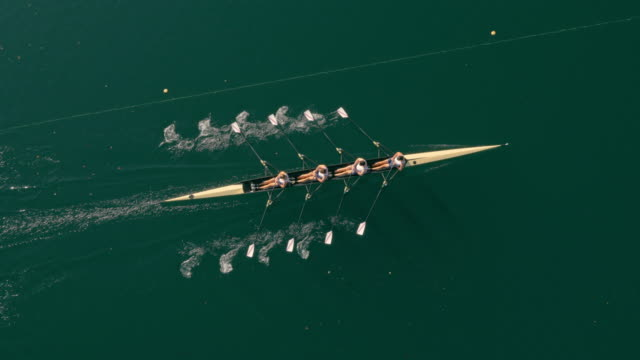 aerial athletes rowing in a quadruple scull across a sunny lake - nautical vessel stock videos & royalty-free footage