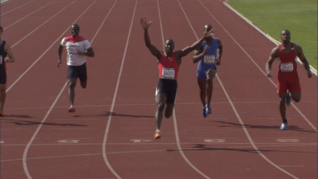 HA WS PAN ZI CU Athletes running in sprint, then winner celebrates / Sheffield, England, UK