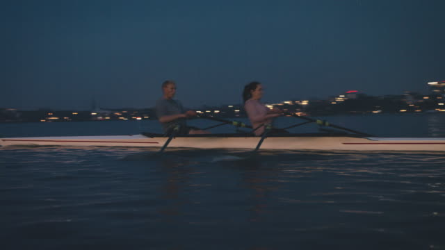 athletes sculling boat in river at night - sculling stock videos & royalty-free footage