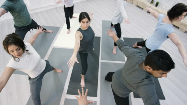 athletic adults doing yoga together in a studio - mindfulness stock videos & royalty-free footage