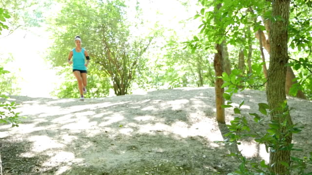 athletic african american woman jogging up hill during off hill run at park - running shorts stock videos & royalty-free footage