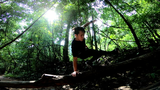 slomo wa athletic asian man jump over a log - tropical rainforest stock videos & royalty-free footage