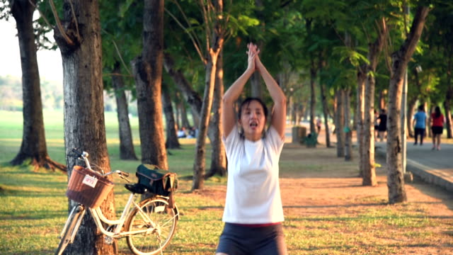 athletic asian woman stretching in public park - realisticfilm stock videos and b-roll footage