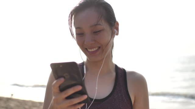 athletische asiatische frau mit smartphone mit kopfhörer - mobilität stock-videos und b-roll-filmmaterial