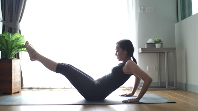 athletic asian young woman doing abdominal crunches while working out at home - aerobics stock videos & royalty-free footage